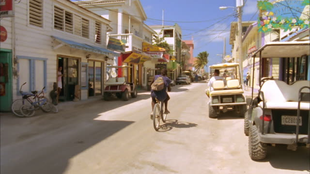 Man rides bicycle along quiet road as woman exits shop and walks onto street, Belize Available in HD.