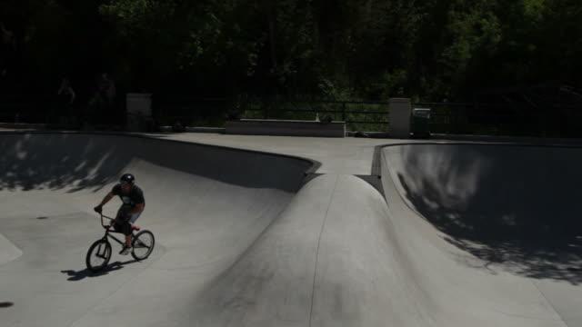 man rides bike around skatepark - sport venue stock videos & royalty-free footage