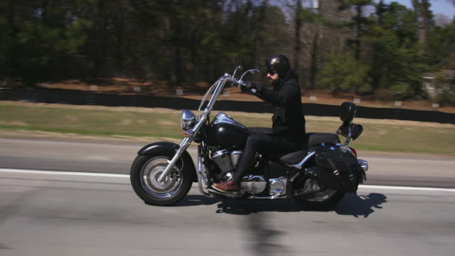man rides chopper on highway, slow motion - motorbike stock videos & royalty-free footage