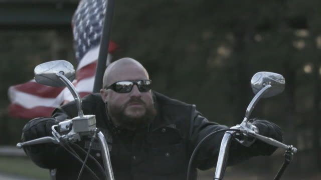 man rides chopper with american flag on back, close up - motorradfahrer stock-videos und b-roll-filmmaterial