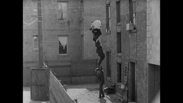 1920 man (buster keaton) rides friend's shoulders to rescue fiance before falling down coal shoot and being married by determined judge - slapstick stock videos & royalty-free footage