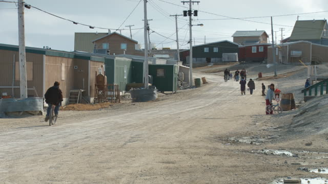 A man rides his a dirt road in the Inuit Town of Igloolik in Canada, children play