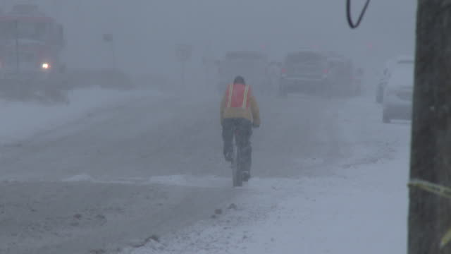 a man rides his bicycle during a blizzard, snowstorm, nor'easter - deep snow stock videos & royalty-free footage