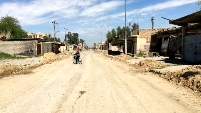 A man rides his bicycle in a road in West Mosul Iraqi forces backed by US and British air support have entered their sixth month of fighting as they...