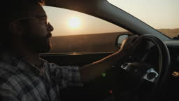 A man rides his car on the sunset background