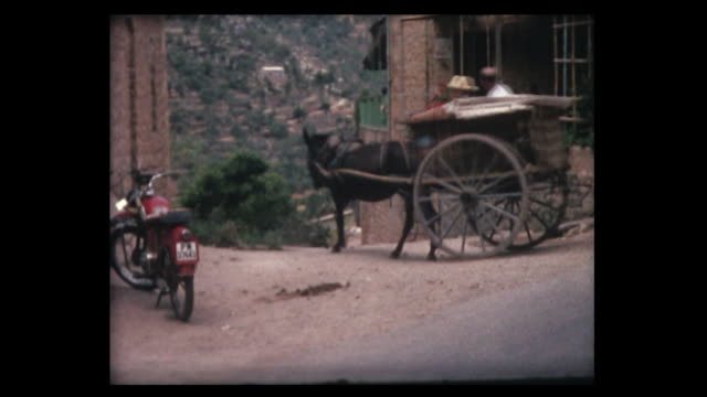 1963 man rides horse carriage along old spanish street - majorca stock videos & royalty-free footage