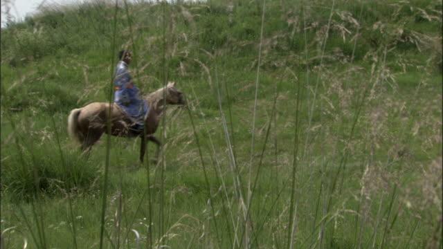 Man rides horse through grassland, Xanadu, Xinjiang Province, China