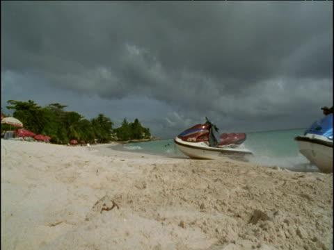 Man rides jet ski up onto beach, Barbados
