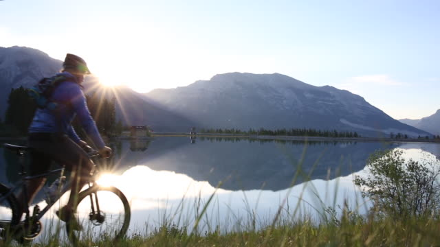 man rides mountain bicycle along edge of mountain lake - sitting stock-videos und b-roll-filmmaterial