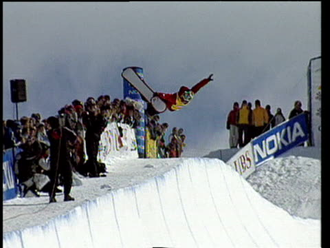 vídeos de stock e filmes b-roll de man rides snowboard on half pipe ramp and performs number of tricks including grabs jumps and turns during snowboarding competition switzerland - roupa de esqui