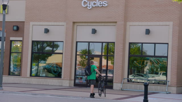 man rides up to local bike shop and walks bicycle into store - centro commerciale suburbano video stock e b–roll