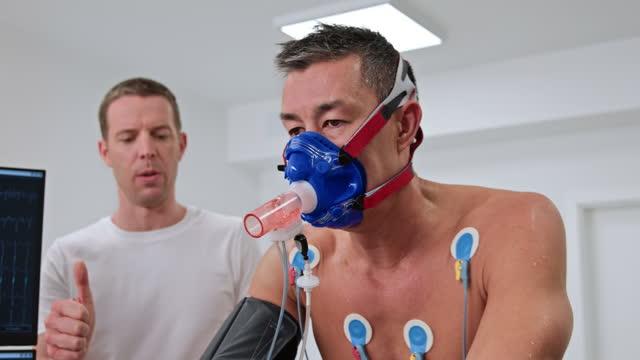 cpetテストで自転車のエルゴメーターに乗ってldの男は、男性医師によって監督されています - 電極点の映像素材/bロール