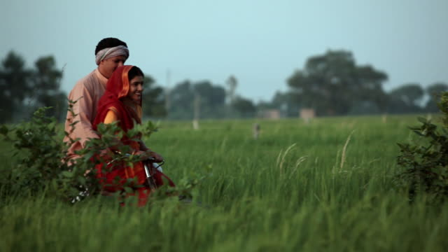 man riding a bicycle with his wife in the farm  - dhoti video stock e b–roll