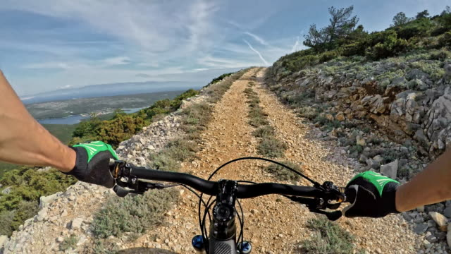 pov man riding a bike on a gravel road above the sea in sunshine - bicycle trail outdoor sports stock videos & royalty-free footage