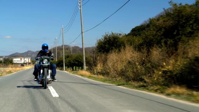 vídeos de stock e filmes b-roll de man riding a custom touring motorcycle in the countryside - bandido