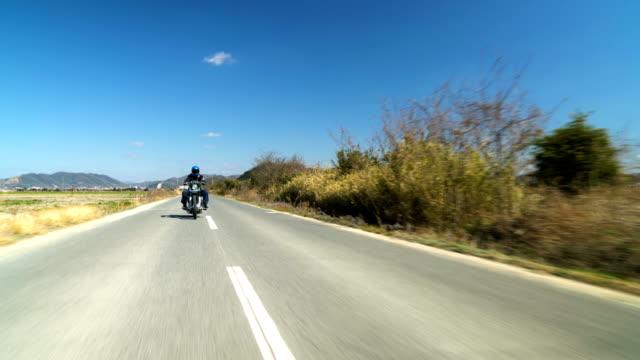 田舎でカスタム ツーリング バイクに乗る男 - バイカー点の映像素材/bロール