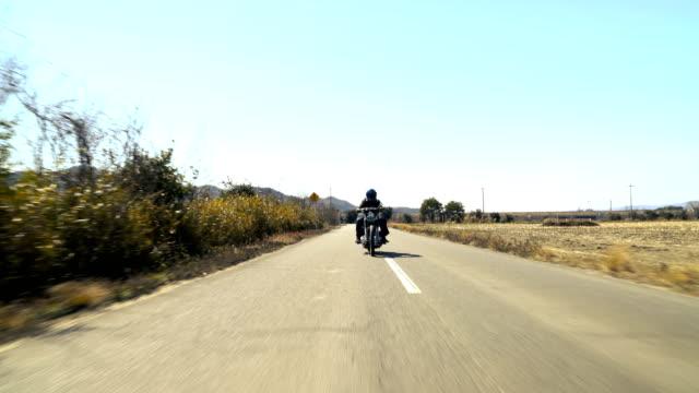 田舎でカスタム ツーリング バイクに乗る男 - 乗物後部から見た視点点の映像素材/bロール