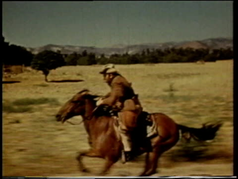 1941 REENACTMENT man riding a galloping horse across a field / United States