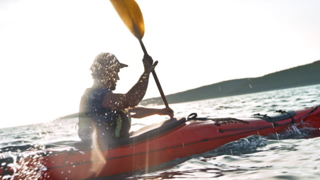 slo mo ts man riding a kayak at sea in sunshine - kayak video stock e b–roll