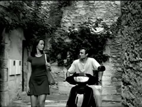 A man riding a motor scooter talks to a woman walking down a village street in France.