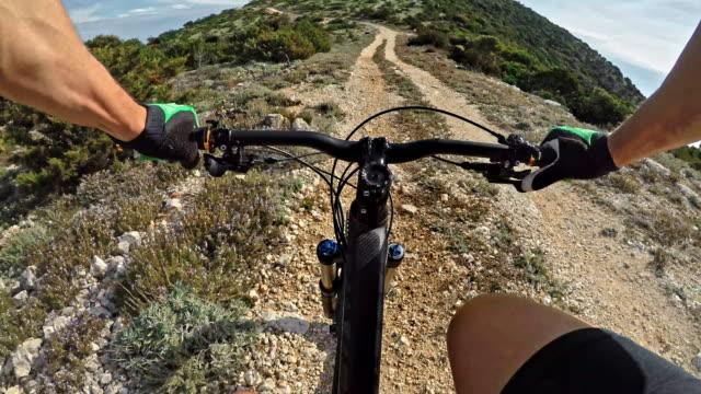 POV-Mann auf einem Mountainbike auf einer staubigen Straße führt über einen Berg