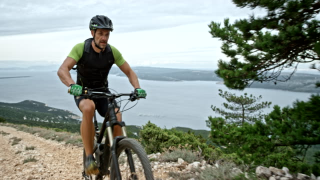 Man riding a mountain bike up the rocky trail overlooking the sea