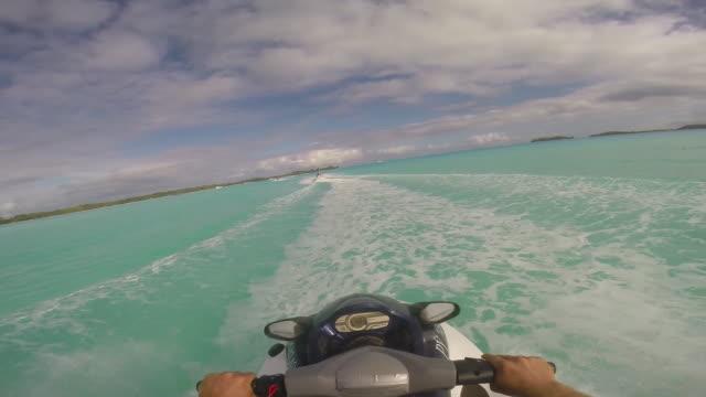 pov of man riding a personal water craft in the lagoon around bora bora island in french polynesia. - slow motion - bora bora stock videos and b-roll footage