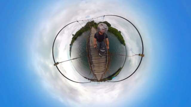 Man riding a scooter on a Tiny Planet suspension bridge - 360°