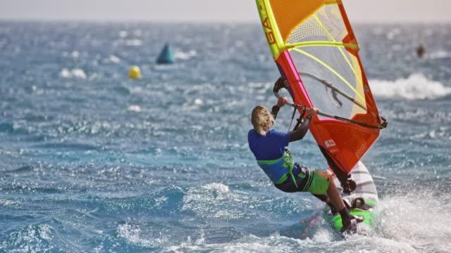 stockvideo's en b-roll-footage met slo mo man rijden een windsurf op winderige zee in zon - windsurfen