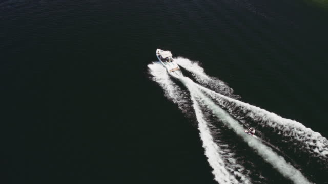 4k aerial: man riding air chair behind a boat - motorboat stock videos & royalty-free footage