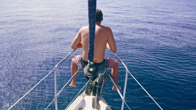 man riding at bow of sailboat over sunny blue ocean, real time - legs apart stock videos and b-roll footage