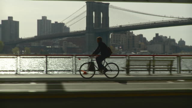 WS TS Man riding bicycle along waterfront bike pathway located under FDR Drive / New York City, New York, USA