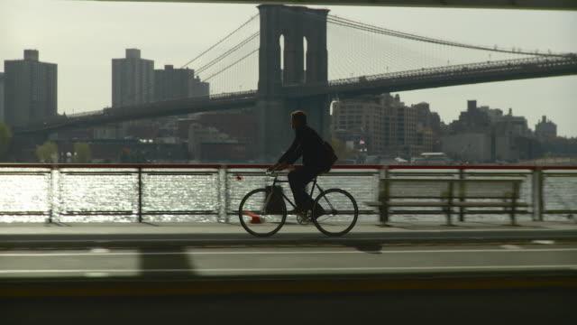 vídeos y material grabado en eventos de stock de ws ts man riding bicycle along waterfront bike pathway located under fdr drive / new york city, new york, usa - side view