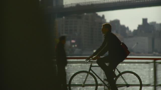 vídeos de stock, filmes e b-roll de ws ts man riding bicycle along waterfront bike pathway / new york city, new york, usa - câmera seguindo movimento