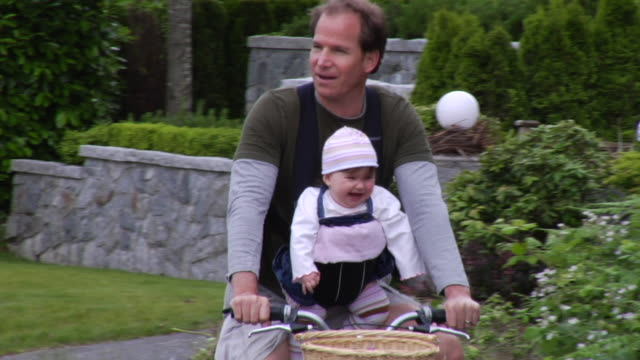 vídeos de stock, filmes e b-roll de ms man riding bicycle down suburban street with baby in carrier on his chest/ vancouver, bc - kelly mason videos