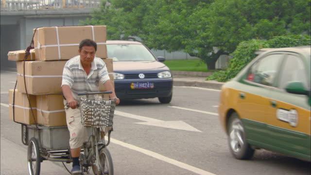MS PAN Man riding bicycle hauling trailer of boxes behind on street, Beijing, Beijing, China