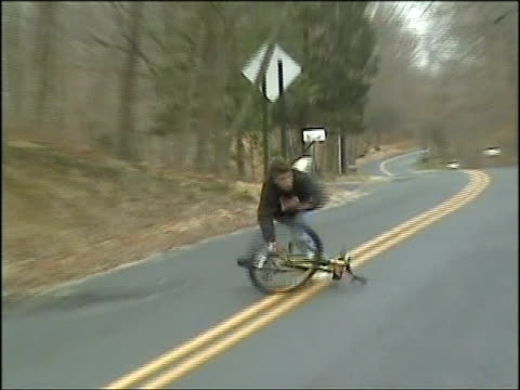 vídeos de stock e filmes b-roll de ms, zo, zi, man riding bicycle, jumping off and falling on road, usa - impacto