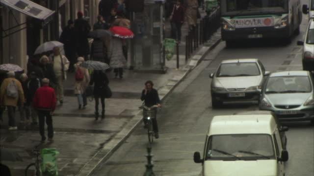 WS HA TS Man riding bicycle on busy street, Paris, France