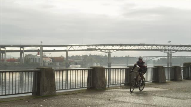 ws man riding bicycle with bridge in background / portland, oregon, usa - portland oregon bike stock videos & royalty-free footage