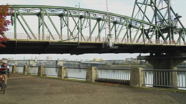 ws pan man riding bicycle with hawthorne bridge in background / portland, oregon, usa - see other clips from this shoot 1695 stock videos & royalty-free footage