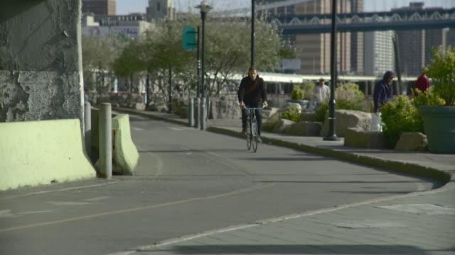 WS CU Man riding bike on curving bike pathway below Brooklyn Bridge / New York City, New York, USA
