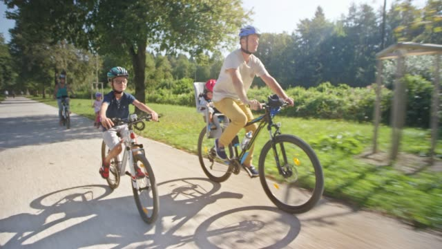 ts man riding bike with his family in the sunny park and his toddler son is sitting in the back seat on his bike - five people stock videos & royalty-free footage