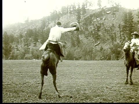 1924 b/w ws man riding bucking bronco wearing chaps + holding cowboy hat in hand / south dakota, usa - bucking stock videos & royalty-free footage