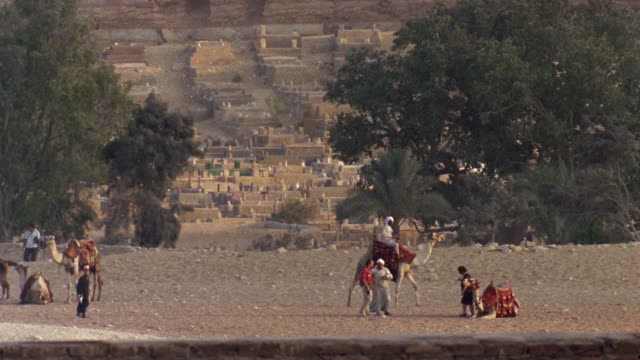 ws man riding camel past villagers and sitting camel / egypt - 1992 stock videos & royalty-free footage