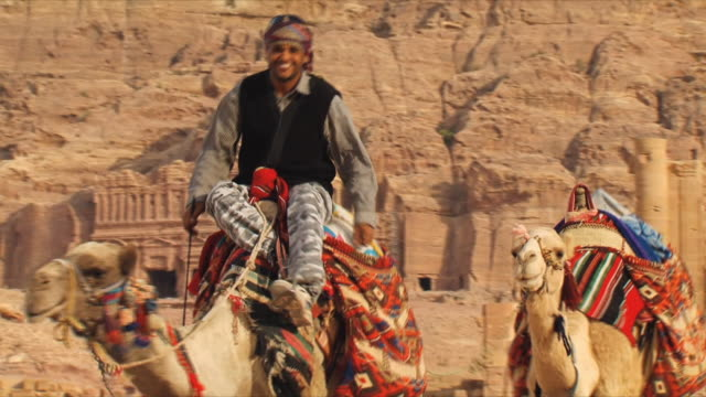 ms man riding camel (camelus dromedarius), urn tomb at ancient city of petra in background / jordan - 6th century bc stock videos and b-roll footage