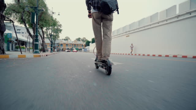 man riding electric kick scooter in city - motor scooter stock videos & royalty-free footage