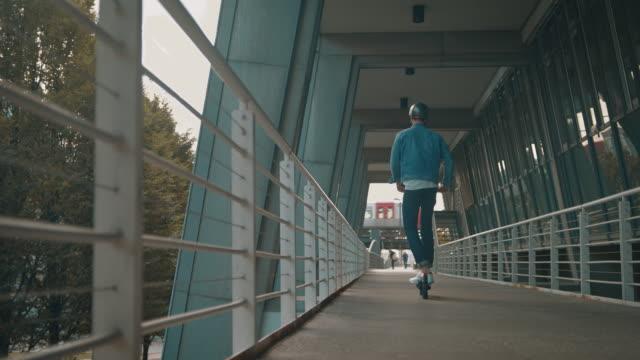 vídeos y material grabado en eventos de stock de hombre montando patinete eléctrico en el puente - ciclomotor vehículo de motor