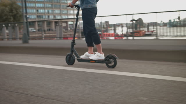 man riding electric push scooter on bridge - motor scooter stock videos & royalty-free footage