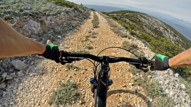 pov man riding his mountain bike on a gravel and dusty road in sunshine - 10 seconds or greater stock videos & royalty-free footage