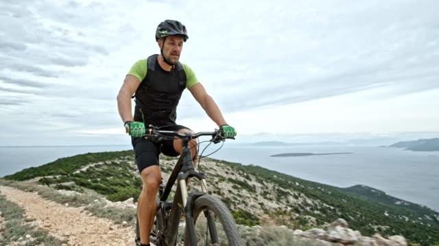 Man riding his mountain bike on a mountain ridge overlooking the sea